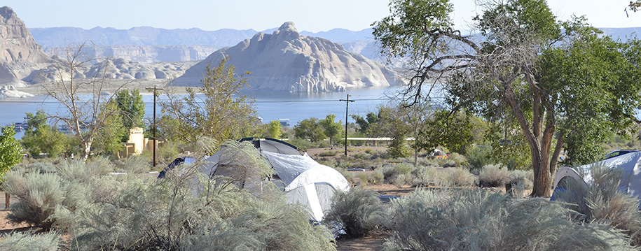 Two tents are pitched among scrubby bushes. Lake Powell and cliff are in the background.