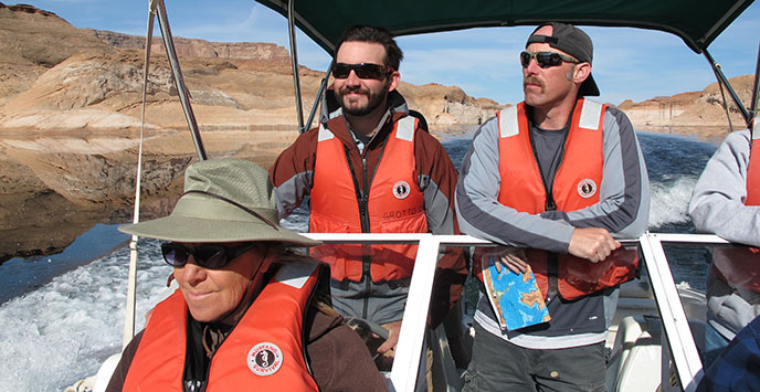 Three people wearing lifejackets are on a boat traveling across Lake Powell.