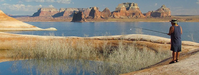 A man in shorts fishes in a natural hole carved in the sandstone. The hole is full of water and the tops of trees. Lake Powell surrounds him. Cliffs are in the background.