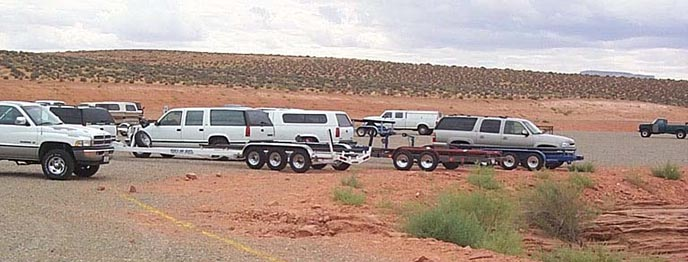 SUVs and Pickup trucks towing empty boat trailers are parked near orange sand.