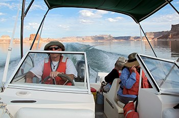 Man wearing life jacket, hat, and sunglasses drives powerboat over Lake Powell with seated passengers also wearing life jackets