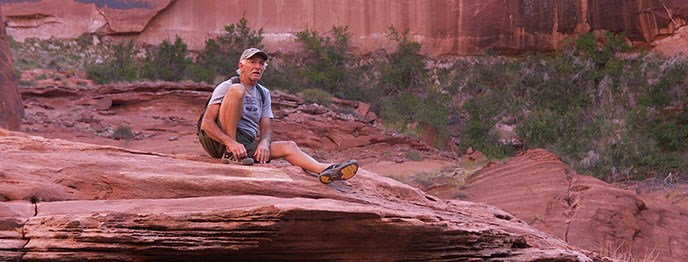 A man adjusts his shoe while sitting on the edge of a cliff. He is wearing a hat and a backpack.
