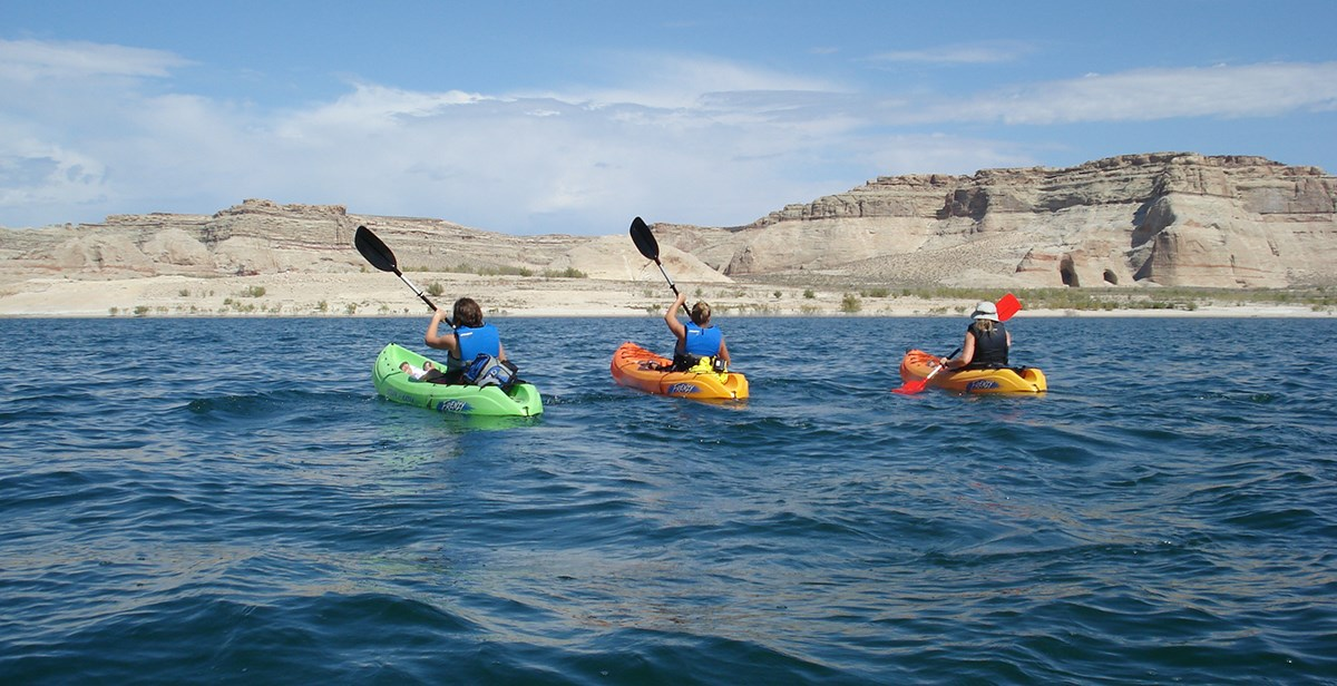 Group of three kayakers paddle on Lake Powell
