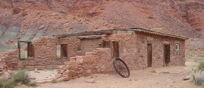 A structure made of rocks with wooden door frams and window frames sits in front of a similarly colored cliff. The structure is falling apart on one side. A wagon wheel leans against one of the window frames.
