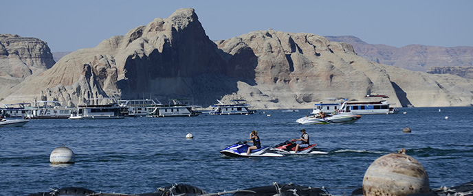 Two people on personal watercrafts ride across the water in an area busy with boats. They are wearing lifejackets. A large rock cliff is in the background.
