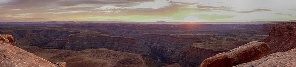 Panoramic view of canyons, rive, and mountain at sunset