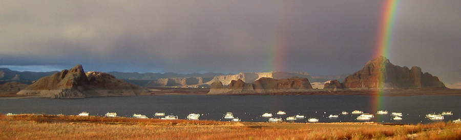 Panoramic view of houseboats on lake Powell. A double rainbow arcs over the scene.