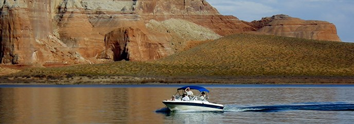 A boat glides across the still water with a sandstone cliff in the background.