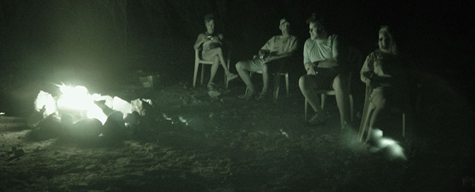 At night, four people sit around a roaring campfire on the beach.