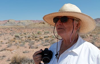 Woman wearing proper desert attire and holding camera looks over landscape
