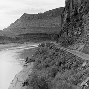 Historic photo of a road alongside the Colorado River surrounded by cliffs.