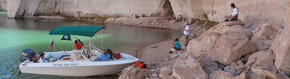 "A white boat labeled ""National Park Service"" is beached in a sandstone alcove. Lifejackets and gear are on board. Four people are on the beach."