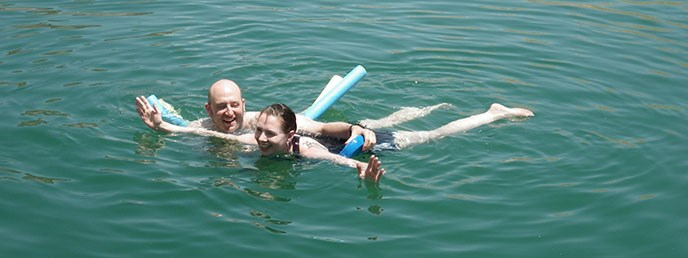 A man and a woman swimming with two long swim noodles.