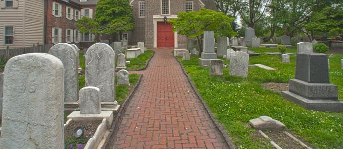 Color photo of a portion of the Gloria Dei cemetery with tombstones in the foreground lining both sides of a narrow brick walk that leads up to the red doors of the church in the background.
