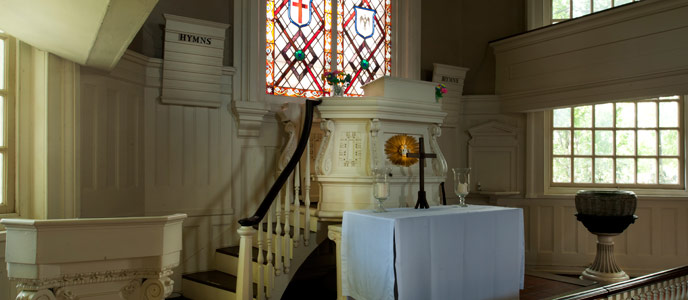 Color photo of the interior at Gloria Dei Church, showing a cross standing on a white cloth covered table, with a large stained glass window behind.