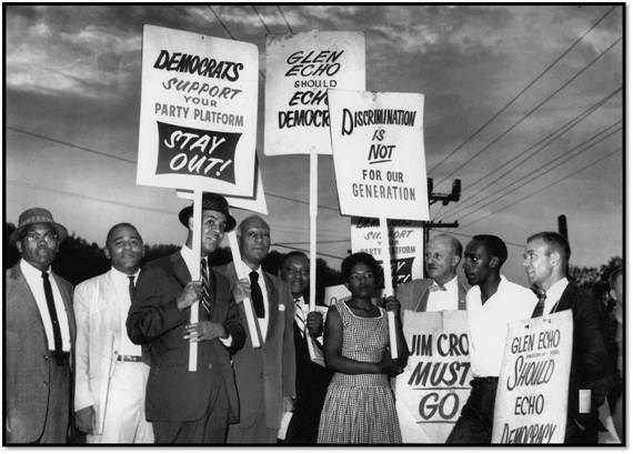 Protest signs with black and white group members plus Gwendolyn Britt