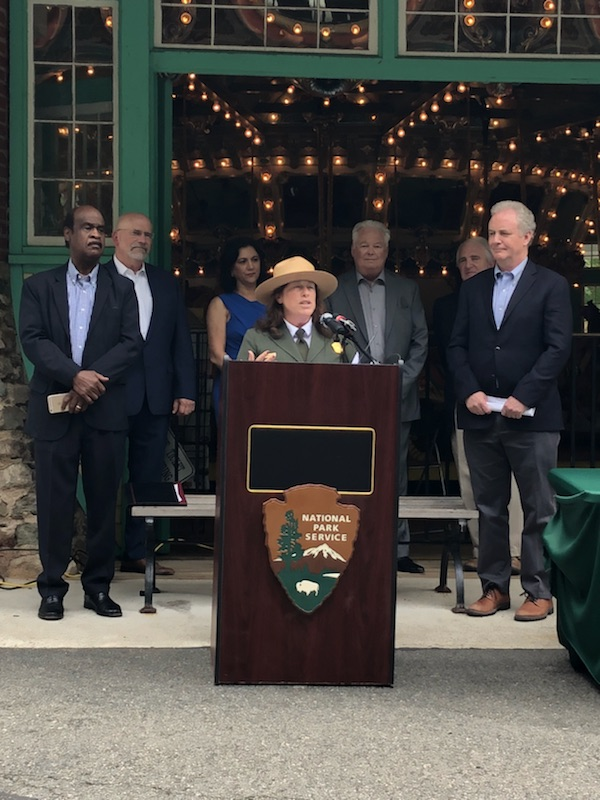 Ranger speaks at a podium with local officials and historic carousel in the background.