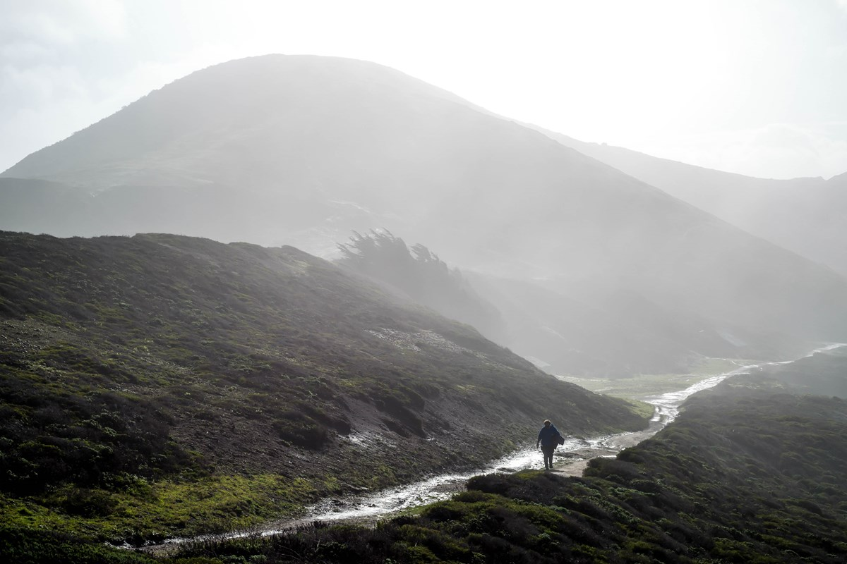 A hiker walks along Mori Point Trail in the morning fog.