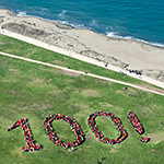 Aerial photo of people grouped together to form a 100 on Crissy Field