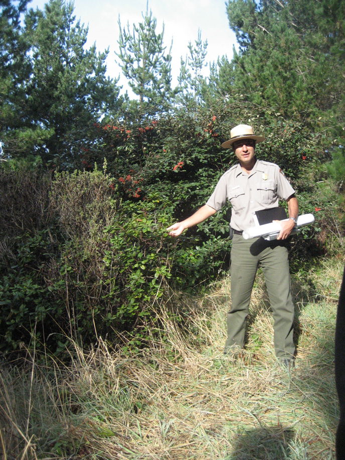 NPS Ranger, George Durgerian, leads a Rancho hike. In this image, he is explaining a type of shrub growing in the area.
