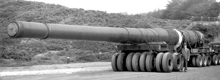historic photo of large metal gun barrel on tractor wheels