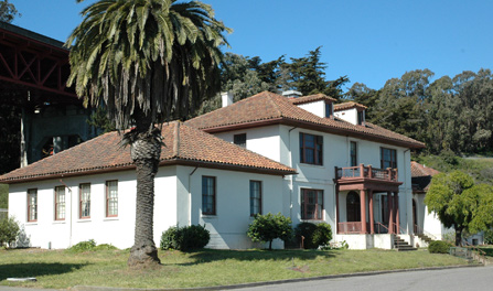 view of small Mission Revival building with white walls and red roof tiles