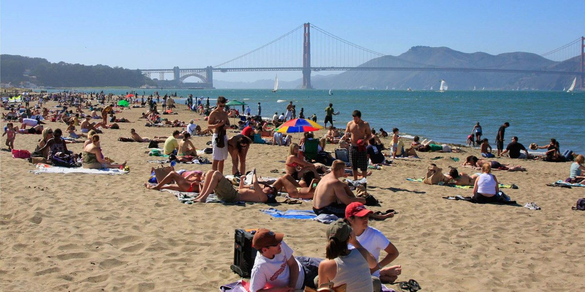 crowded crissy beach on a sunny day in front of golden gate bridge