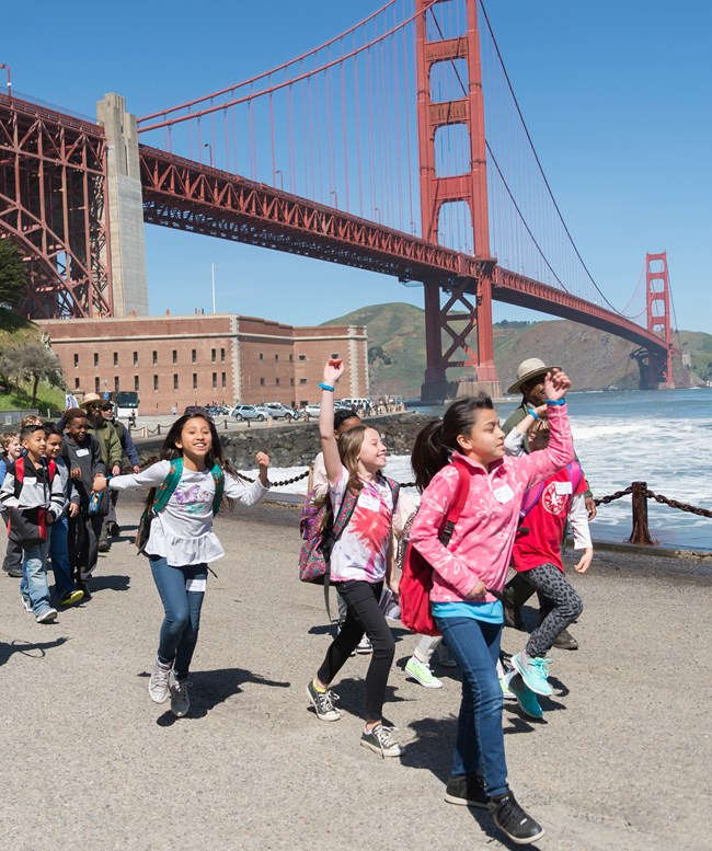 group of kids walk down road in front of Fort Point and golden gate bridge