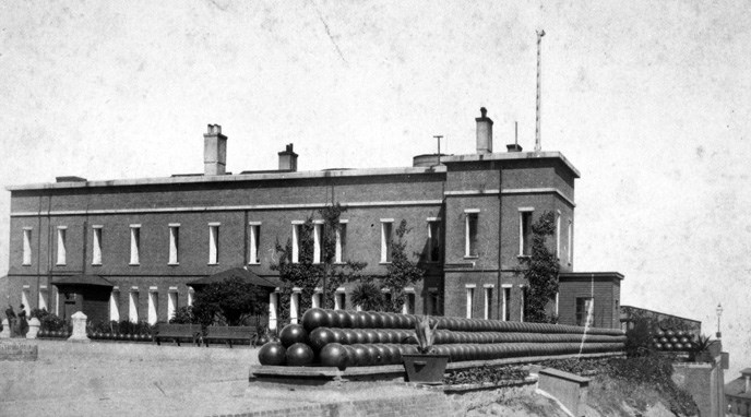 historic photo of brick military building surrounded by rows of decorative cannon balls