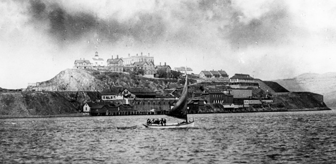 historic photo of Alcatraz with small boat in foreground and island in background