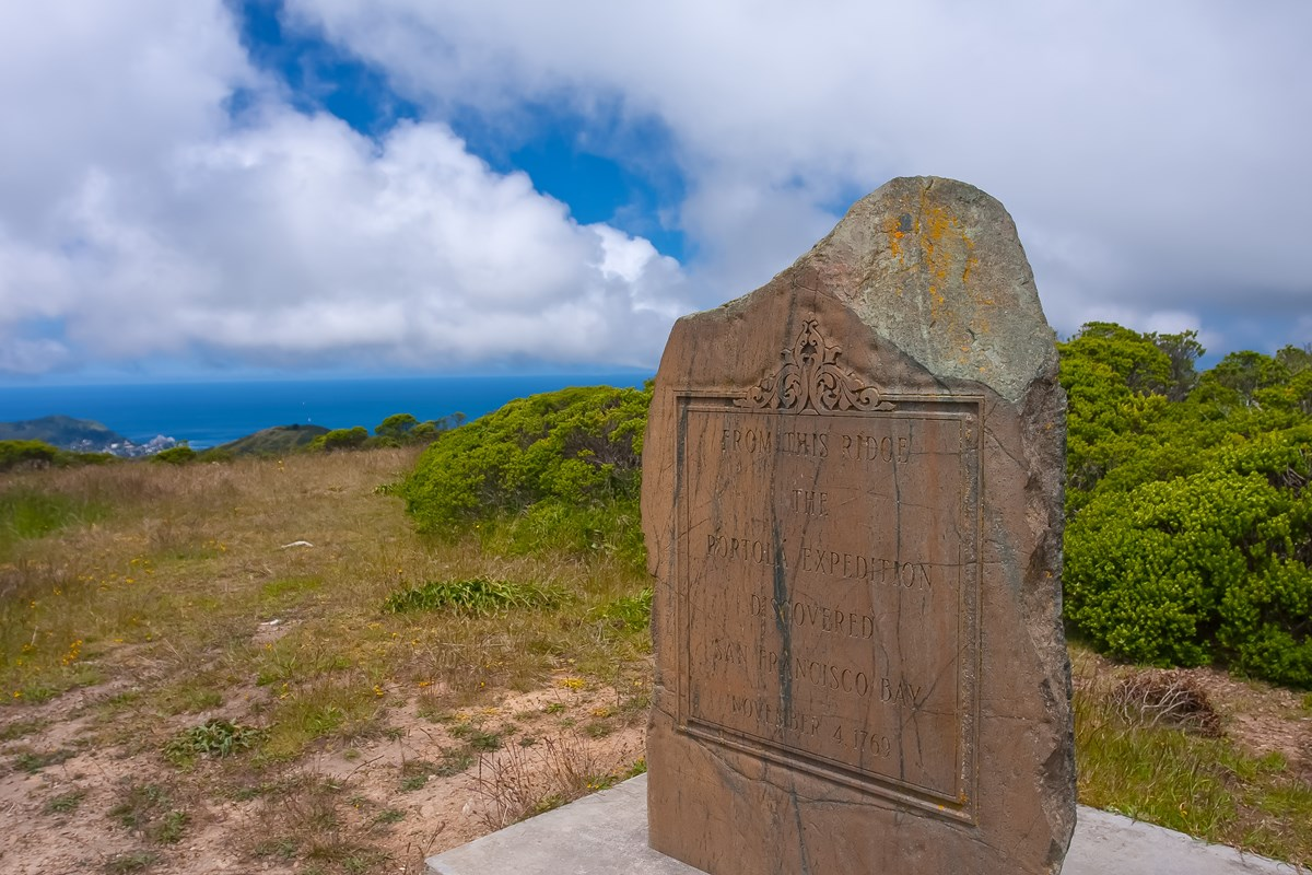 Inscribed serpentine rock monument at top of Sweeney Ridge, with ocean in the distance behind.