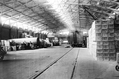 large warehouse facility filled with crates and a freight car