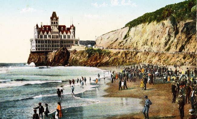 historic colored postcard with ornate building on bluff overlooking crowded beach