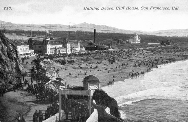 historic postcard showing long, crowded beach with amusement park buildings in the background