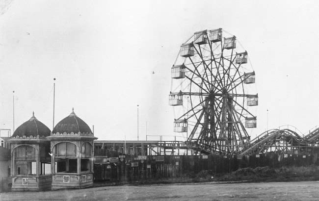historic photo of ferris wheel, low rollercoaster and decorative ticket booths