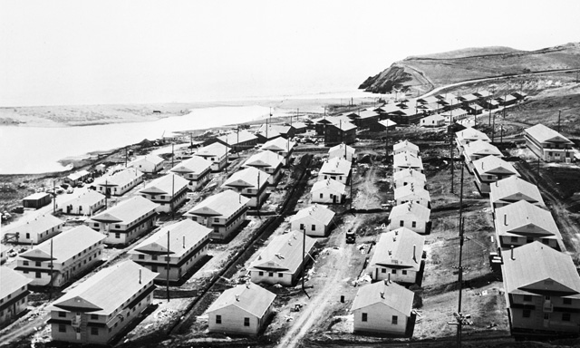rows of wooden army barracks near beach