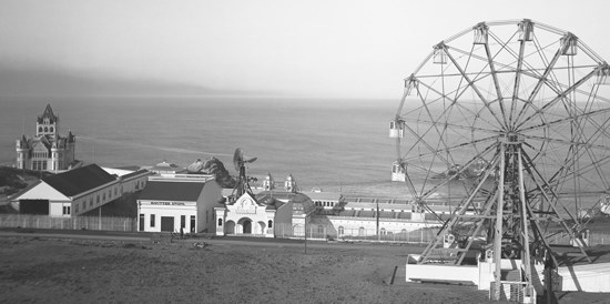 historic image of ferris wheel and small buildings at edge of Pacific Ocean