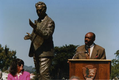 man speaking at podium with statue in background