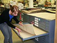 woman pulling maps from flat file drawer