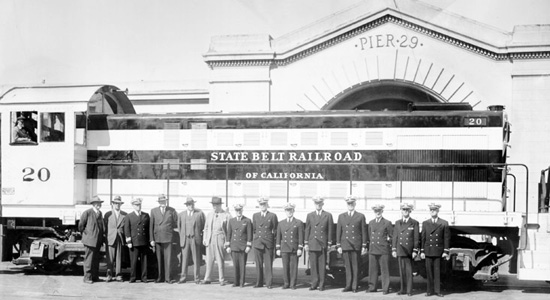 men in uniform in front of diesel train at San Francisco Pier