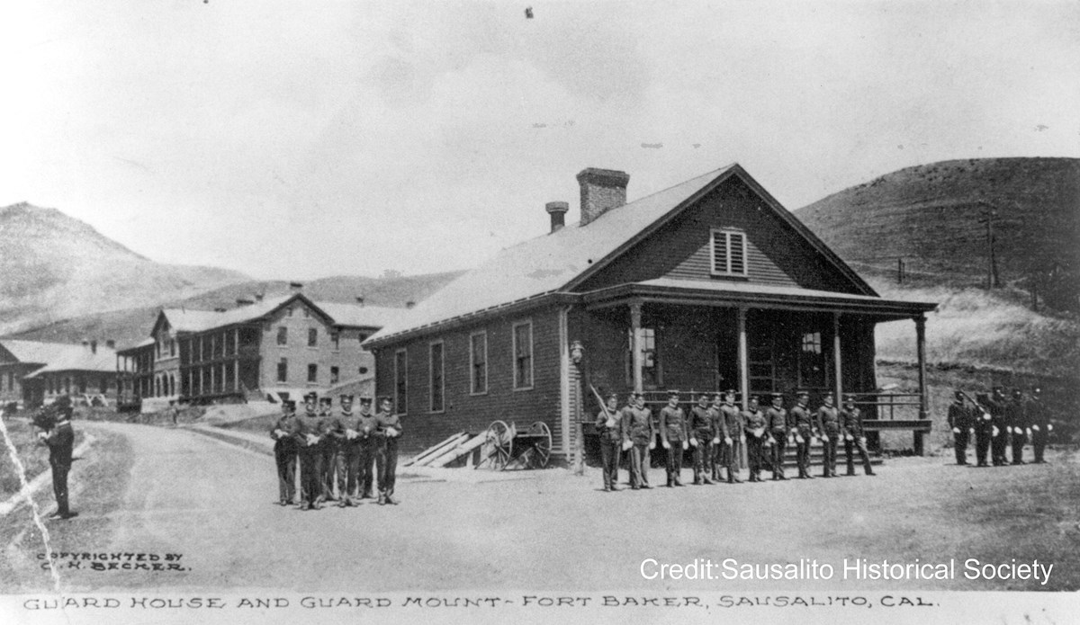 soldiers standing at attention in front of brick building
