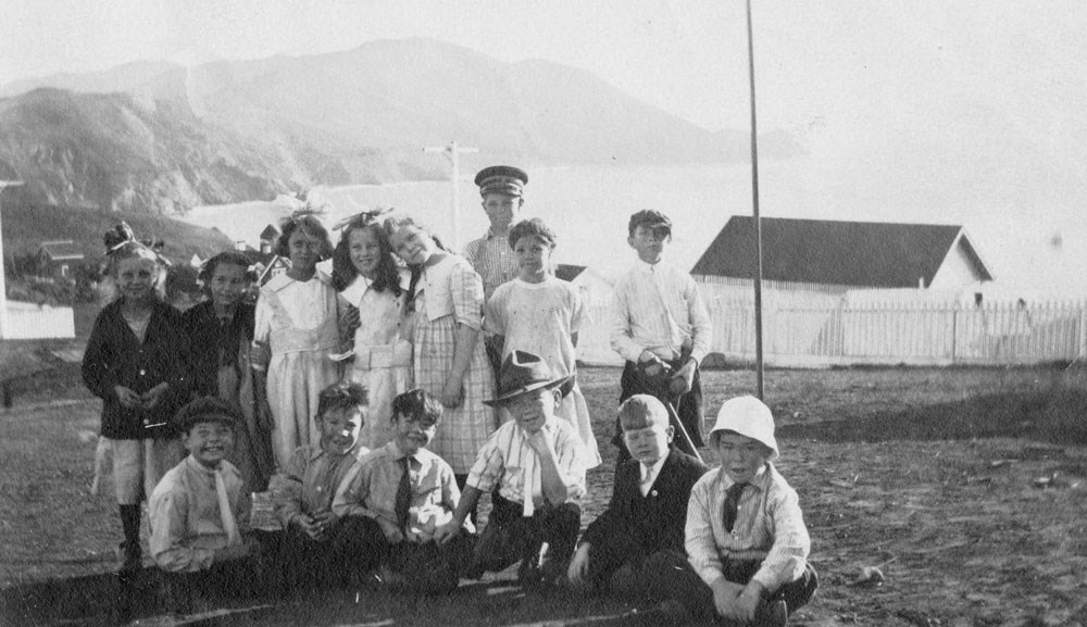 a group  of smiling boys and girls near ocean and cliffs