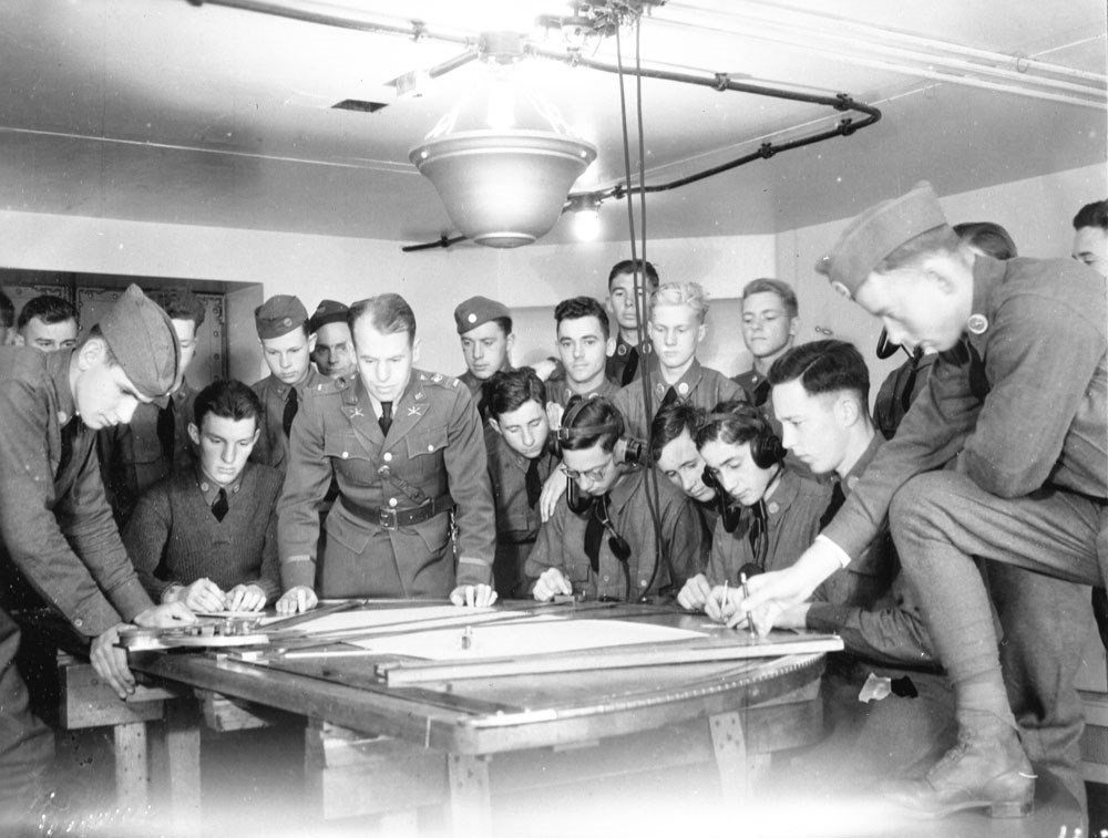 a crowded room of soldiers reviewing a table