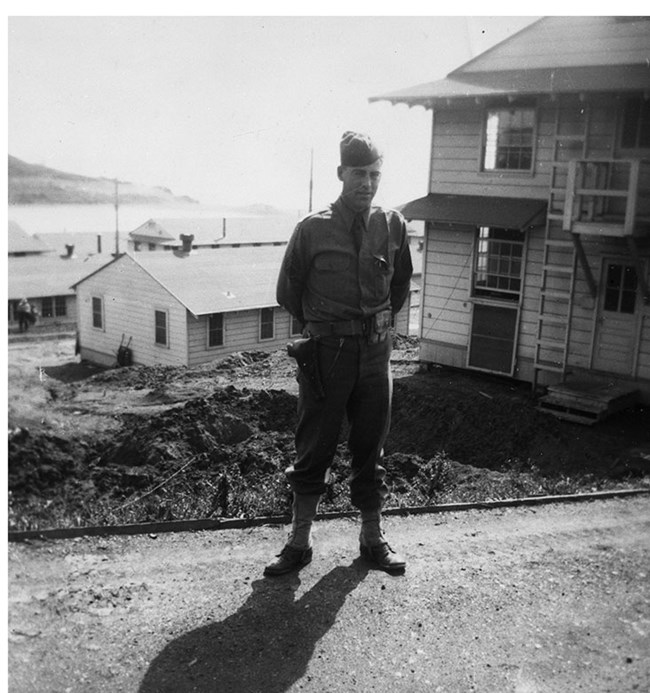 soldier standing at attention in front of army barracks