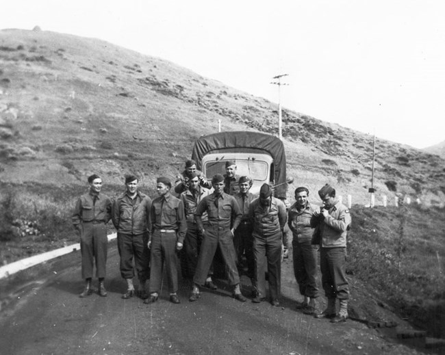 a group of soldiers at ease, standing in front of a truck