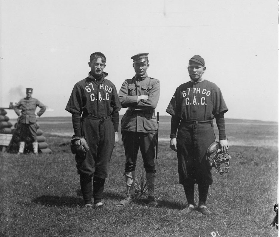 soldiers in old fashioned baseball uniforms holding catcher's mitts