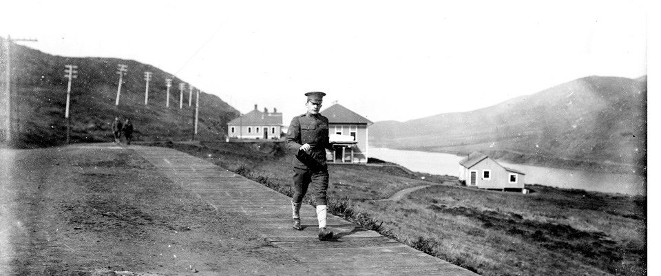 man in uniform walking on rural road