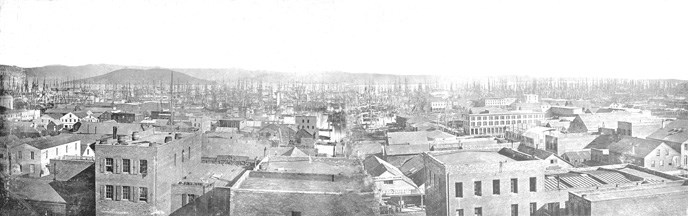 A view across rooftops towards Angel Island, with ships masts along the waterfront from 1853.