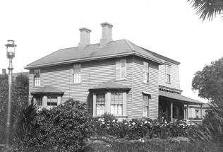 historic image of wood-frame house with gambrel roof, two chimney and bay windows