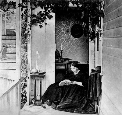 historic photo of Jessie Benton Fremont sitting and reading on her front porch